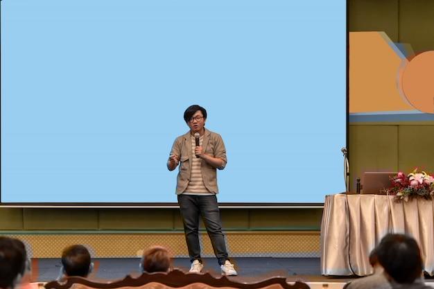 Zbliżenie portret azjatykci mówca z przypadkowym kostiumem na scenie nad prezentacja ekranem