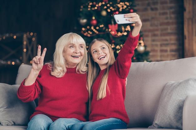 Zbliżenie portret babci mała mała uczennica co selfie pokaz vsign w urządzonym domu