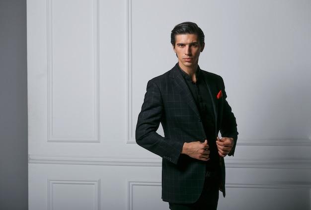 Zbliżenie portret biznesowy mężczyzna nosić czarny elegancki garnitur portret na ścianie neoklasycznej, patrząc z boku. skopiuj miejsce.