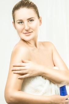 Zbliżenie portret brunetki kobiety za pomocą kremu po prysznicu
