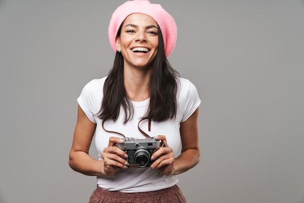 Zbliżenie portret brunetki ładnej turystycznej kobiety w berecie, śmiejącej się i fotografującej na retro aparacie na białym tle nad szarą ścianą