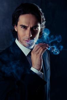 Zbliżenie portret brutalnego mężczyzny trzymającego cygaro z dymem w ręku