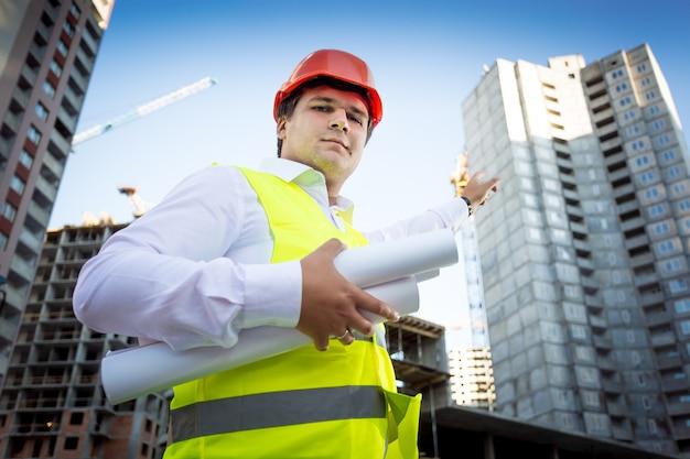 Zbliżenie portret brygadzisty w kasku pokazujący plac budowy w budowie