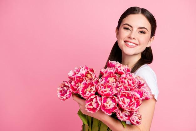 Zbliżenie portret całkiem ładna dziewczyna trzyma w rękach bukiet kwiatów świątecznych
