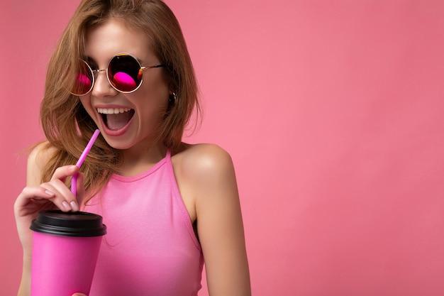 Zbliżenie portret całkiem młoda pozytywna blond kobieta nosi różowy top i kolorowe okulary przeciwsłoneczne