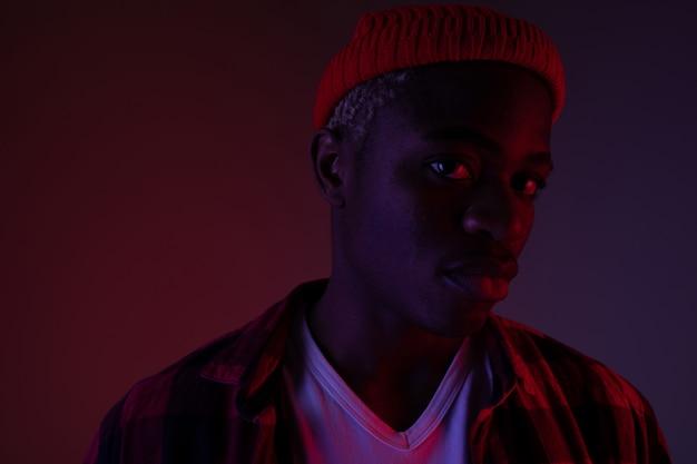 Zbliżenie portret czarujący przystojny czarny człowiek patrząc na kamery w świetle neonu w cieniu