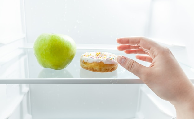 Zbliżenie portret dłoni wybierając między jabłkiem a pączkiem w lodówce