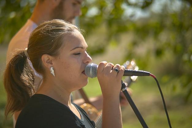 Zbliżenie portret dziewczyny śpiewa do mikrofonu