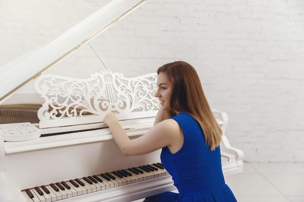 Zbliżenie portret dziewczyny w niebieskiej sukience siedzi przy fortepianie