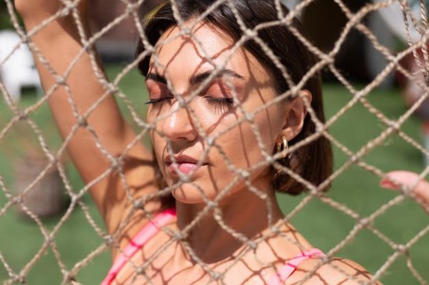 Zbliżenie portret dziewczyny widziany przez sieć w upalny słoneczny dzień na zewnątrz