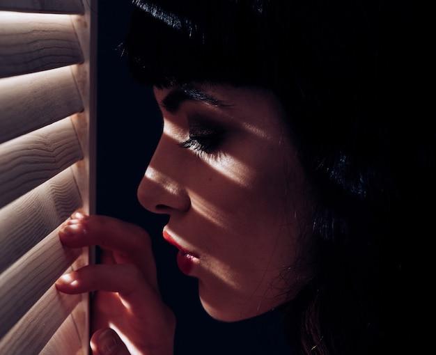 Zbliżenie portret dziewczyny z zmysłowej twarzy światła i cienia