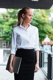 Zbliżenie portret inteligentnej kobiety biznesu z laptopem stojącym na szklanym balkonie na zewnątrz