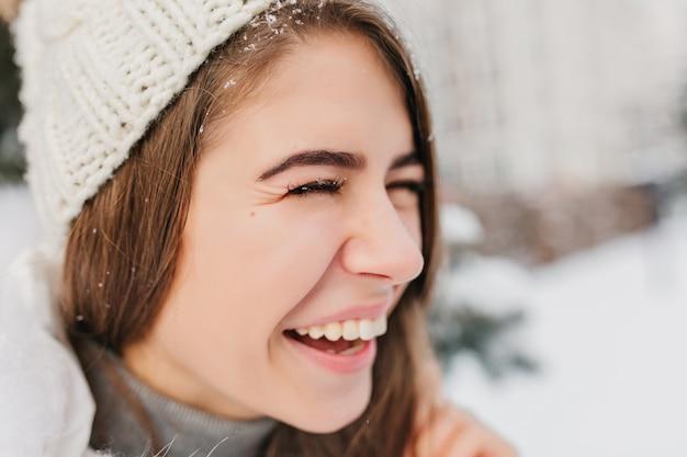 Zbliżenie portret jaskrawe pozytywne emocje twarzy radosnej kobiety w ciepły biały kapelusz z dzianiny, śmiejąc się na ulicy pełnej śniegu. prawdziwe emocje, płatki śniegu, dobra zabawa, cieszenie się zimą.