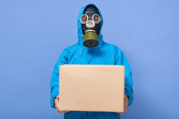 Zbliżenie portret jest ubranym munduru i maski gazowej mienia kartonu pudełko w rękach chemik naukowiec