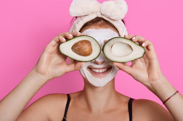 Zbliżenie portret kobiety 20s z idealną skórą, trzymając awokado przed oczami na białym tle na różowym tle, opieka zdrowotna, zabiegi kosmetyczne w domu.