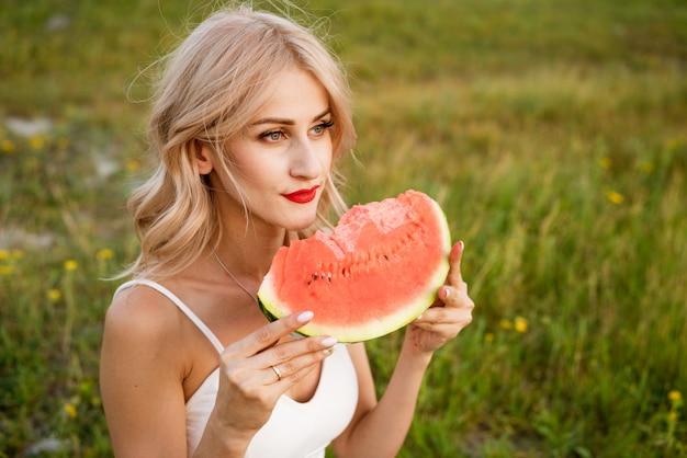 Zbliżenie portret kobiety gryzie arbuza w przyrodzie piękna dziewczyna o kaukaskim wyglądzie zjada arbuza na pikniku
