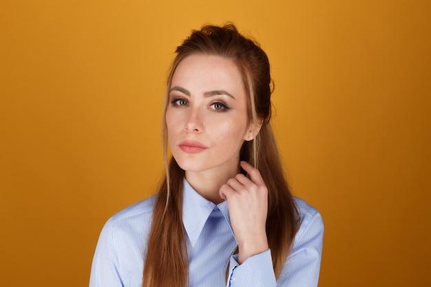 Zbliżenie portret kobiety ładna yong z jasnym makijażem w studio na białym tle na żółtym tle.
