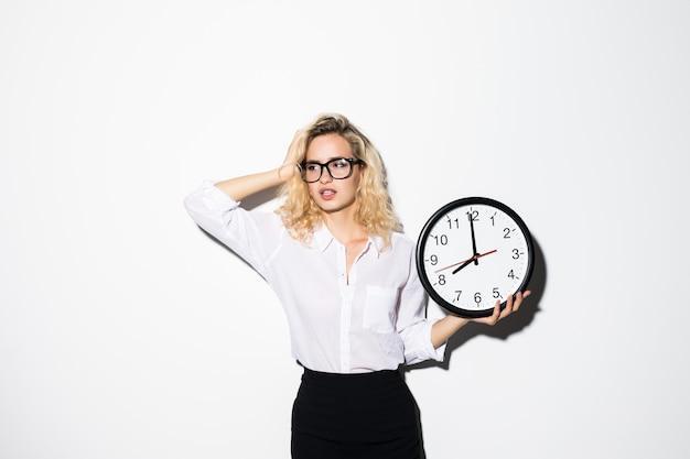 Zbliżenie portret kobiety, pracownik, trzymając zegar patrząc z niepokojem, naciskany brakiem, kończy się czas na białym tle białej ściany. wyraz twarzy człowieka, emocje, reakcja, życie korporacyjne.