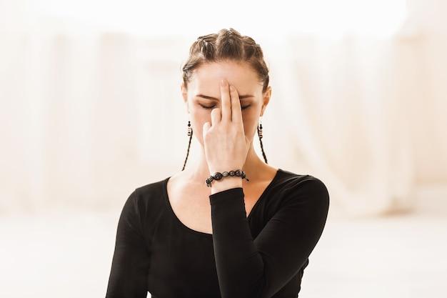Zbliżenie portret kobiety praktykującej jogę, przedstawiającej symbol jnana mudry na twarzy podczas oddychania pranajamą nadi shodhana