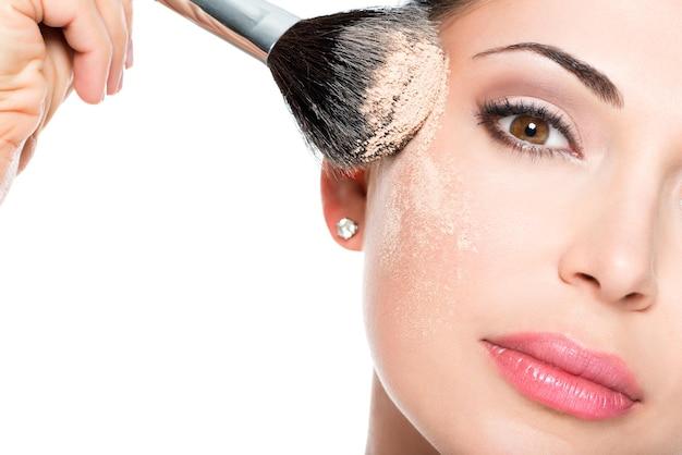 Zbliżenie portret kobiety stosując suchy podkład kosmetyczny tonalny na twarzy za pomocą pędzla do makijażu.