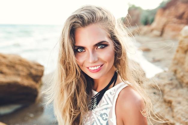 Zbliżenie portret ładna blondynka w słońcu pozowanie na kamienistej plaży. ona uśmiecha się do kamery