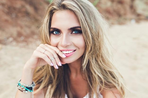 Zbliżenie portret ładna blondynka z długimi włosami i niebieskimi oczami, pozowanie na kamienistej plaży. ona uśmiecha się do kamery.