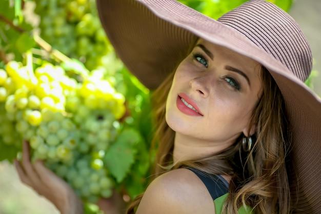 Zbliżenie portret ładna młoda kobieta, która trzyma kiść winogron w jej rękach