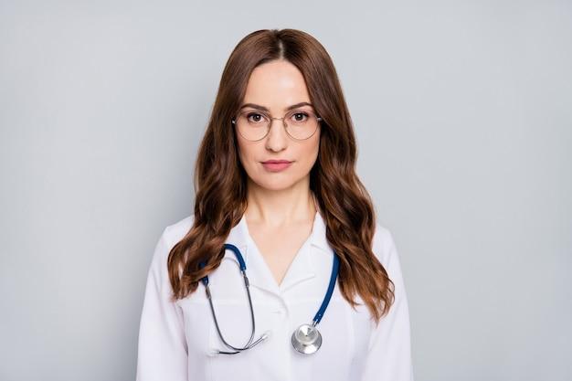 Zbliżenie portret ładne, atrakcyjne, wykwalifikowane, faliste włosy doc pielęgniarka specjalista fonendoskop stetoskop noszący specyfikacje pomoc medyczna na białym tle na szarym tle pastelowych kolorów
