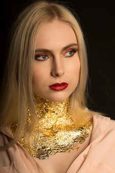 Zbliżenie portret luksusowej młodej modelki z czerwonymi ustami i złotą folią na szyi