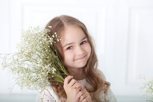 Zbliżenie portret mała dziewczynka z bukietem łyszczec. urocza dziewczynka z blond włosami z kwiatami w dłoniach. 8 marca, międzynarodowy dzień kobiet, dzień matki. słodkie dziecko z bukietem.