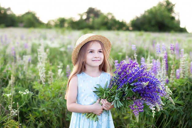 Zbliżenie portret małej dziewczynki w polu łubiny. dziewczyna trzyma bukiet purpurowi kwiaty w ścianie pole łubiny. zdjęcie letnich kwiatów. koncepcja dzieciństwa. skopiuj miejsce