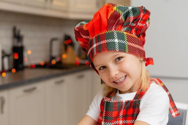 Zbliżenie portret małej szczęśliwej uśmiechniętej blondynki w stroju kucharza w kuchni