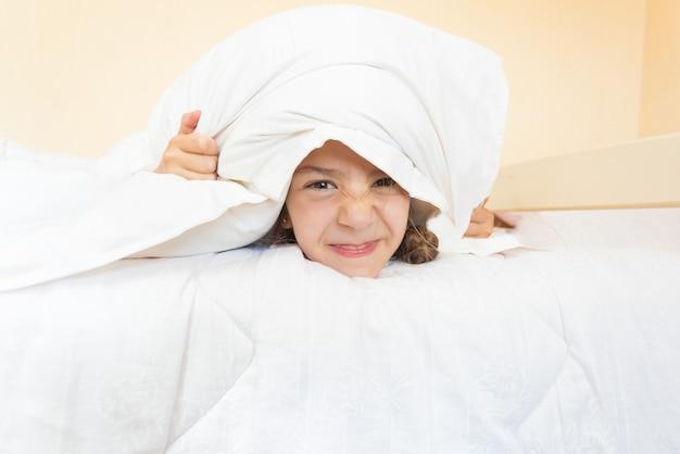 Zbliżenie portret małej zły dziewczynki leżącej w łóżku z poduszką na głowie