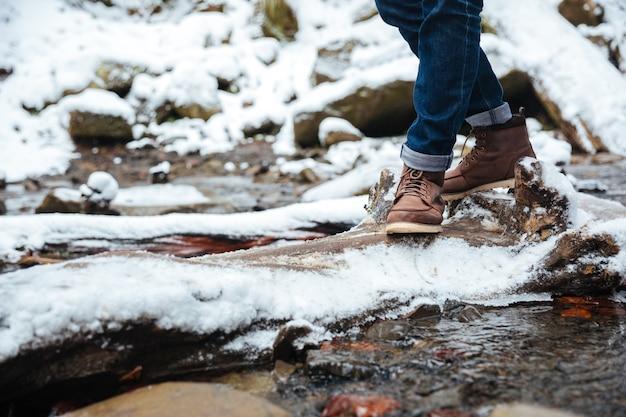 Zbliżenie portret męskich nóg z rzeką i śniegiem