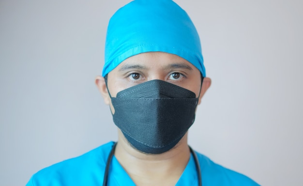 Zbliżenie portret mężczyzny lekarza noszącego maskę i czapkę