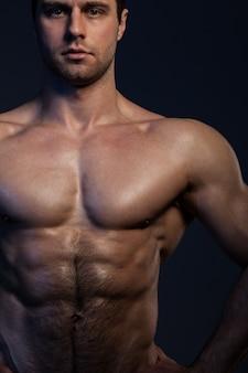 Zbliżenie portret mięśniowy facet w zmroku