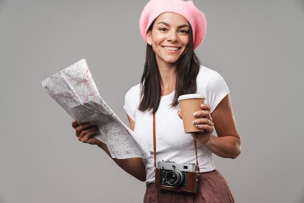 Zbliżenie portret miłej młodej kobiety turystycznej z retro starodawną kamerą i kawą na wynos uśmiechniętą i trzymającą papierową mapę na białym tle nad szarą ścianą