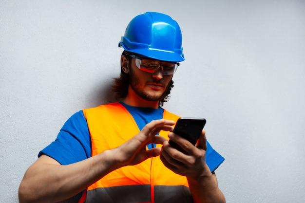 Zbliżenie portret młodego człowieka, inżynier pracownik budowlany, za pomocą smartfona, noszenie sprzętu bezpieczeństwa na tle szarej ściany z teksturą.