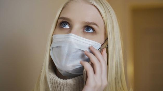 Zbliżenie portret młodej dziewczyny w medycznej masce na twarz rozmawia przez telefon