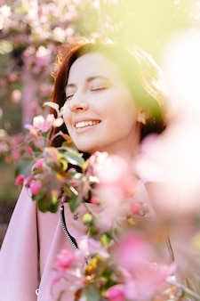 Zbliżenie portret młodej dziewczyny z uśmiechem na twarzy stojącej wokół kwitnących drzew róż