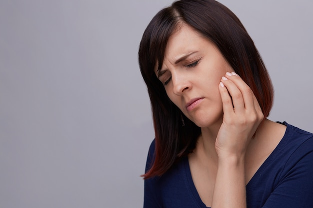 Zbliżenie portret młodej kobiety cierpiące na ból zęba, trzymając palce do szczęki i zamykając oczy z bólu.