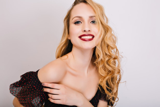 Zbliżenie portret młodej kobiety, ładna blondynka uśmiechnięta, ciesząc się, po sesji zdjęciowej. ma ładną miękką skórę, makijaż, długie kręcone włosy. ubrana w czarną sukienkę, z otwartymi ramionami.