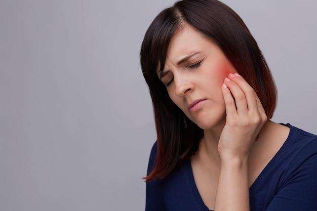 Zbliżenie portret młodej kobiety na szarym tle cierpi na ból zęba.