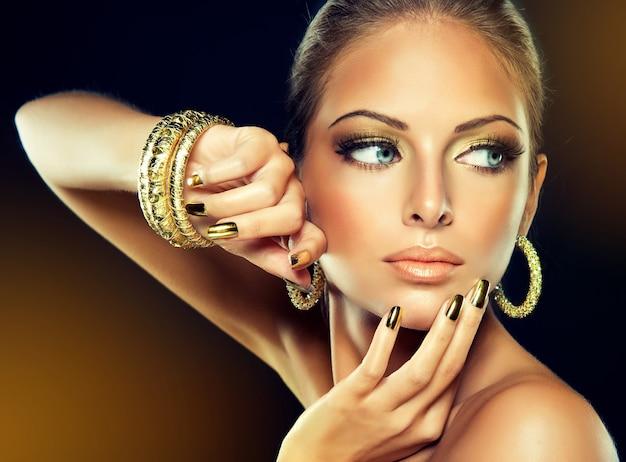Zbliżenie portret młodej kobiety w eleganckim wieczorowym makijażu, duże rzęsy i pozłacany lakier do paznokci z eleganckim gestem dłoni