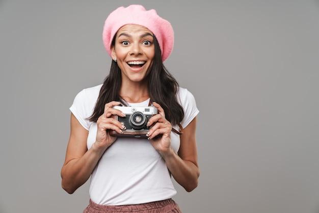 Zbliżenie portret młodej ładnej kobiety turystycznej w berecie, śmiejąc się i fotografując na retro aparacie izolowanym na szarej ścianie