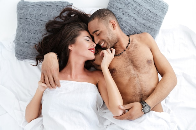 Zbliżenie portret młodej pary romantycznej przytulającej się i całującej, leżącej na białym łóżku