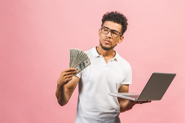 Zbliżenie portret, młody udany biznesmen african american zarabianie pieniędzy z internetu, trzymając w ręku gotówkę, laptop w innym