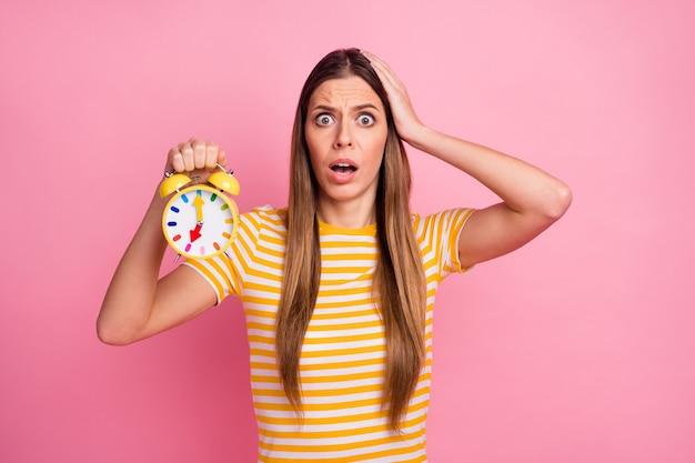 Zbliżenie portret niezadowolenie zmartwiona dziewczyna trzyma w rękach zegar