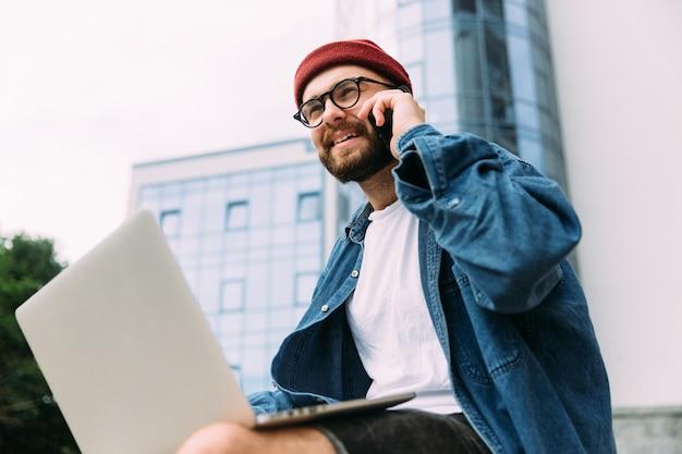 Zbliżenie portret nowożytny brodaty męski modniś opowiada na telefonie i używa laptop w tym samym czasie w eyeglasses.