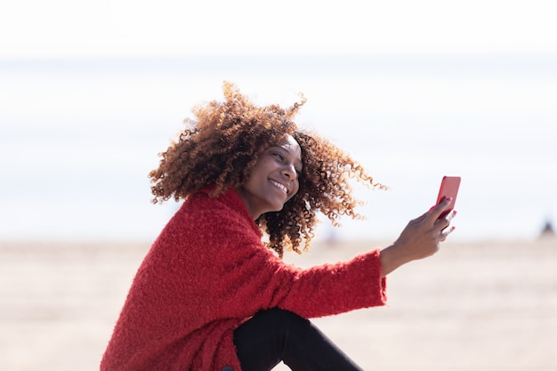 Zbliżenie portret pięknej afrykańskiej kobiety siedzącej na zewnątrz, biorąc selfie